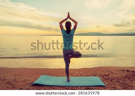 Young woman doing yoga exercise in pose of tree on beach at sunset in summer, rear view