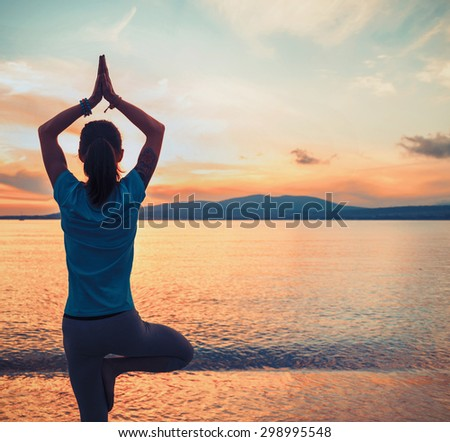 Young woman doing yoga exercise in pose of tree on beach on background of sea at sunset in summer. Space for text in right part of image