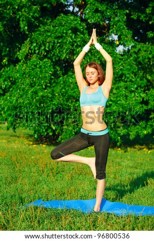 Young woman doing yoga exercise on green park - stock photo