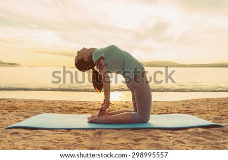 Young woman doing yoga exercise on sand beach on background of sea at sunset in summer