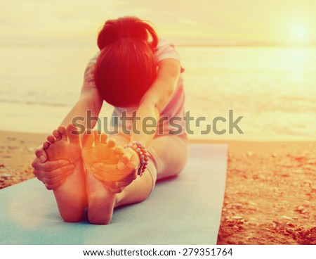 Young woman doing yoga exercise on summer beach at sunset. Image with sunlight effect - stock photo