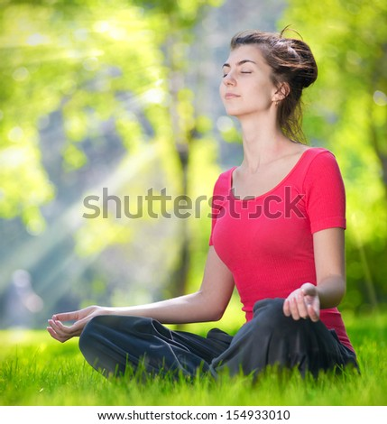 Young woman doing yoga exercises at the summer green city park. In the lotus posture close up - stock photo