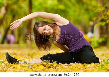 Young woman doing yoga exercises in the autumn city park. Fall