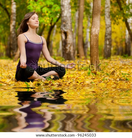 Young woman doing yoga exercises in the autumn city park lake. Fall with mirror in water