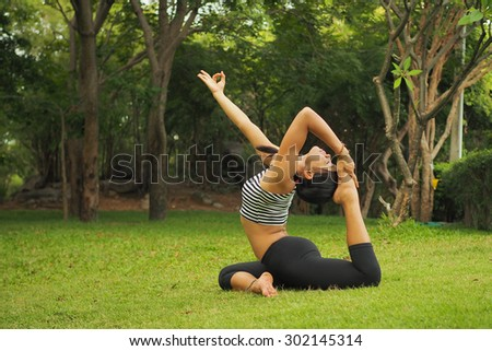 Young woman doing yoga exercises in the garden park