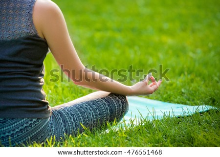 Young woman doing yoga exercises in the summer city park.