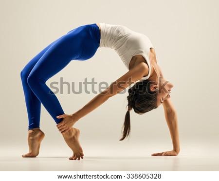 Young woman doing Yoga exercises. studio. Bridge pose - Urdhva Dhanurasana - stock photo