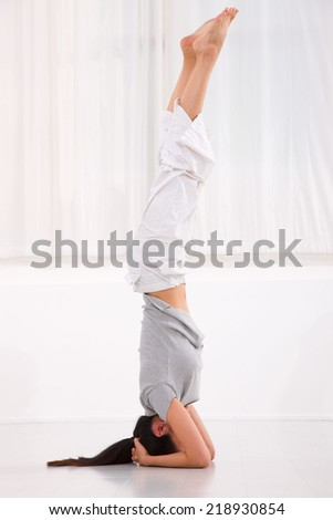 Young woman doing yoga headstand pose - stock photo