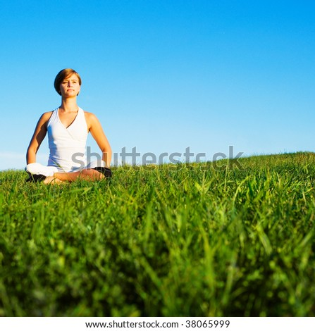 Young woman doing yoga in a sunny meadow, from a complete series of photos.
