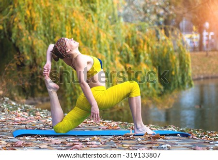 Young woman doing yoga in autumn yellow park