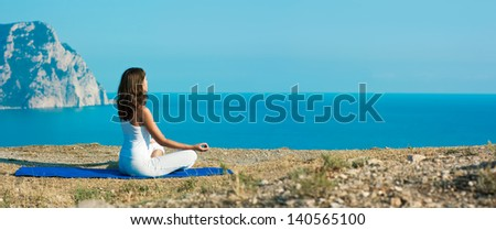 Young Woman Doing Yoga in Lotus Position at the Sea and Mountains. Panoramic View. - stock photo