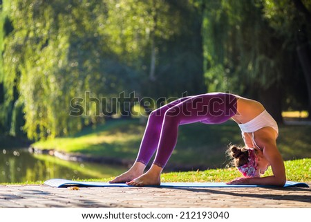 Young woman doing yoga in morning park  - stock photo