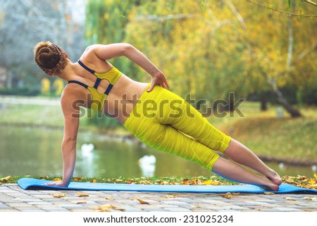 Young woman doing yoga in morning park outdoor. Autumn nature near lake - stock photo