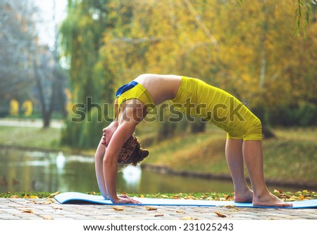 Young woman doing yoga in morning park outdoor. Autumn nature near lake