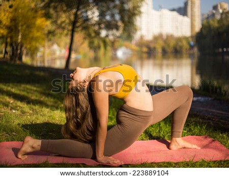 Young woman doing yoga in morning park. Young girl of Caucasian ethnicity outside doing yoga asana in autumn