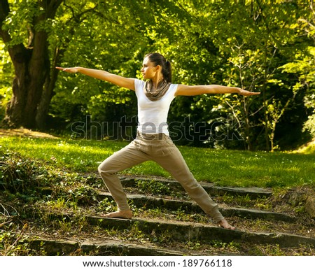 Young woman doing yoga in nature. - stock photo