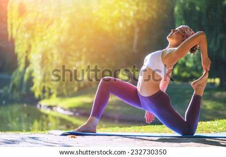 Young woman doing yoga in Park near lake in the morning