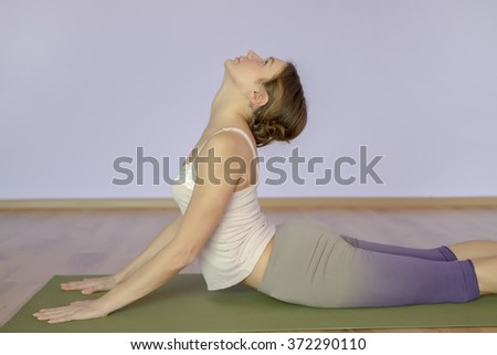 Young woman doing yoga in studio. shot of a young fit woman doing yoga exercises. Full length of a young woman stretching body. - stock photo