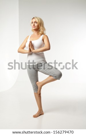 Young woman doing yoga isolated against white background - stock photo