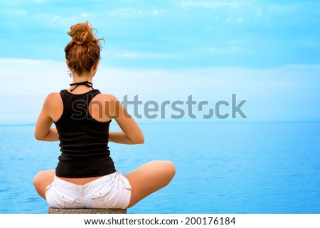 Young woman doing yoga, looking at ocean horizon. - stock photo