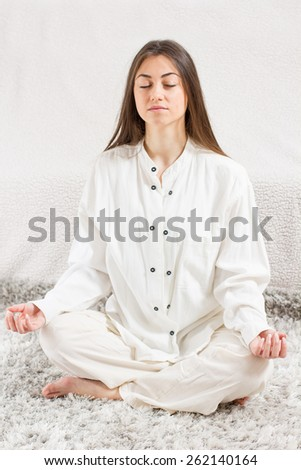 Young Woman Doing Yoga Meditation at home. Caucasian female relaxing .  Healthy Lifestyle.