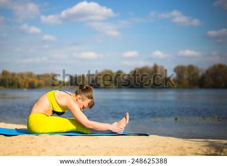 Young woman doing yoga near river - stock photo
