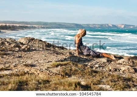 Young woman doing yoga on a rocky seashore. Doing upward facing dog pose - stock photo