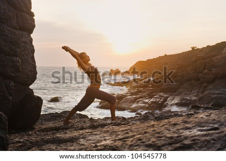 Young woman doing yoga on a rocky seashore. Doing warrior position - stock photo