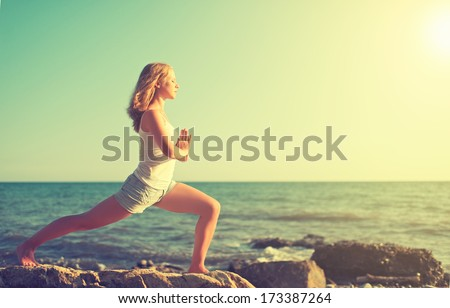 young woman  doing yoga on  coast of  sea on  beach - stock photo