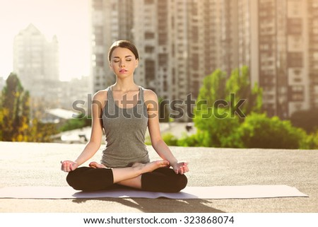 Young woman doing yoga on the mat on the roof, sitting in lotus posture with closed eyes - stock photo