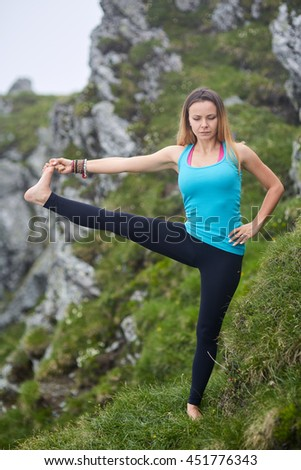 Young woman doing yoga on the summit of the mountain