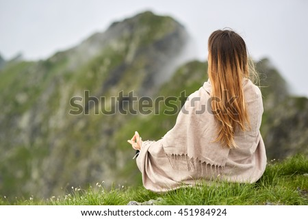 Young woman doing yoga on the summit of the mountain - stock photo