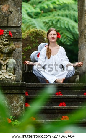 Young woman doing yoga outdoors in tranquil environment - stock photo