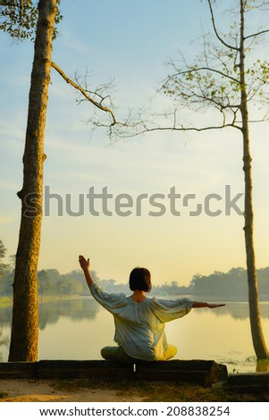 young woman doing yoga outside - stock photo