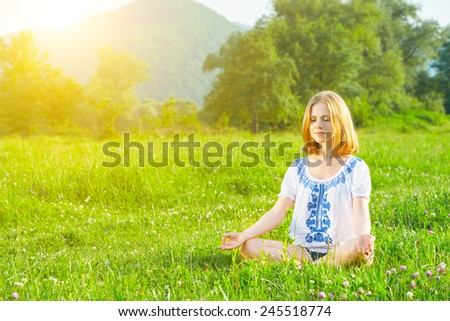 young woman doing yoga, sitting in lotus position on green grass - stock photo