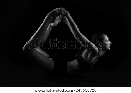 Young woman doing yoga stretches on black background - stock photo