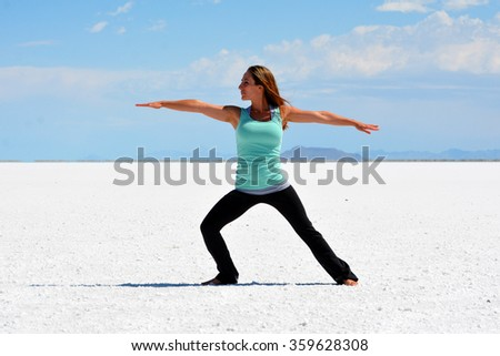 Young woman doing yoga warrior pose on the Bonneville Salt Flats in Utah. - stock photo
