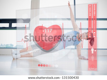 Young woman doing yoga while looking at futuristic interface showing her heartbeat - stock photo