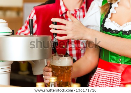 Young woman drawing beer in restaurant or pub, she is the innkeeper - stock photo