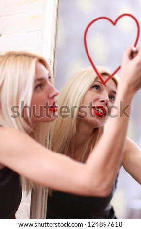 Young woman drawing heart on mirror with - stock photo
