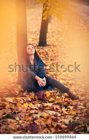 Young woman dreaming under tree. - stock photo