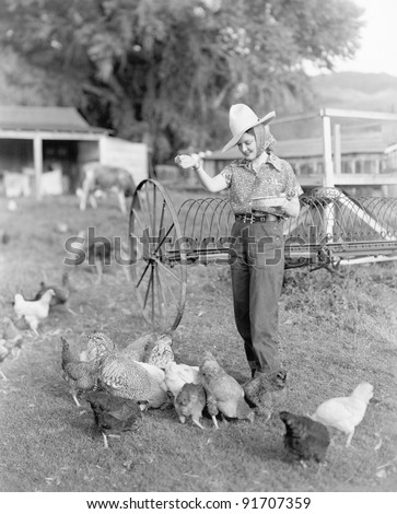 Young woman dressed as a farmer bringing food to the chicken - stock photo