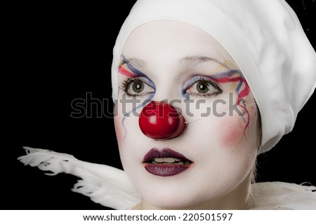 Young woman dressed as a happy clown, with angels wings and white underwear on her head