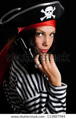 Young woman dressed as a pirate in a black hat holding an gun - stock photo
