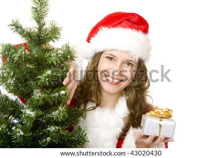 young woman dressed as Santa Claus is standing beside a fir tree, smiles happy and holds a Christmas gift in hand. Isolated on white. - stock photo