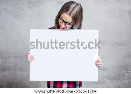 Young woman dressed casually holding white board or empty placard with copyspace standing on the gray wall background.