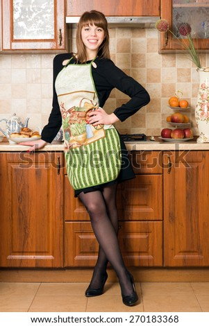 young woman dressed in apron on the kitchen, very cheerful and young - stock photo