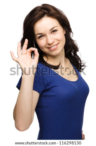 Young woman dressed in blue is showing OK sign, isolated over white - stock photo