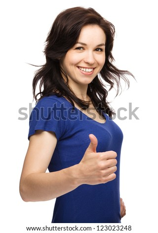 Young woman dressed in blue is showing thumb up gesture, isolated over white
