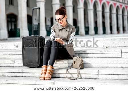 Young woman dressed in coat and glasses with travel bag using phone on the stairs at Republic square in Split city - stock photo